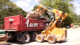 Deere 325 skid steer loading gravel into dump truck