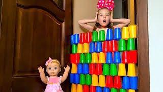 Маша разрушила стенку из разноцветных стаканчиков которую построила кукла Бэлла