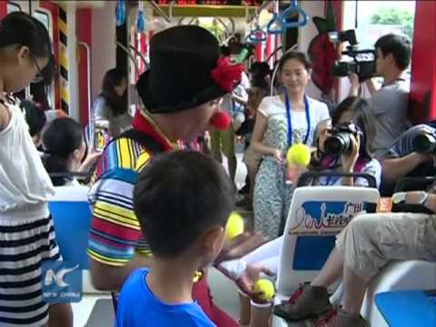 "RAW: ""Happy Clowns"" entertain children on tramcar in S. China"