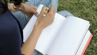 Over the shoulder shot of a beautiful girl sitting in a park and writing in a diary