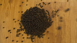Closeup shot of aromatic black pepper grains falling on a wooden table