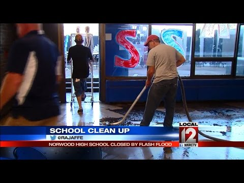Norwood school employees and volunteers work to clean up after flooding