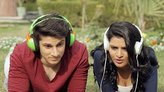 Close up shot of a couple with headphones lying in a park and watching a scary movie together, making faces and giving various expressions