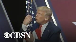 Trump hugs and kisses the American flag at CPAC 2020