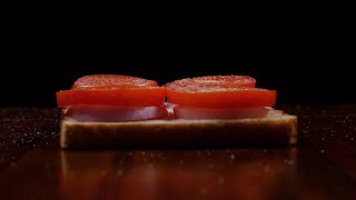 Slow motion shot of salt being sprinkled over a vegetable sandwich