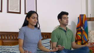 Young Indian couple doing yoga together sitting on bed