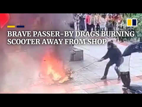 Brave passer-by drags burning scooter away from shop in China