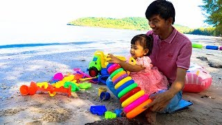 Nora Plays with Stacking Ring Toys At the Beach