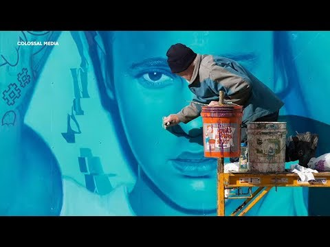 Artists dangle from buildings to hand paint massive billboards | In Our Backyard