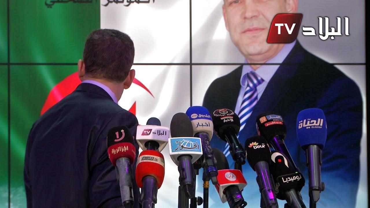 صحفية تقوم بتصحيح الشعار المكتوب على لافتة الراغب في الترشح للرئاسيات سليمان بخليلي