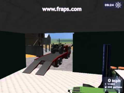 tow truck unloading tractor in workshop.avi