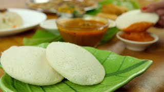 Close up of woman hands eating fresh steamed Idli with the tomato chutney - food concept