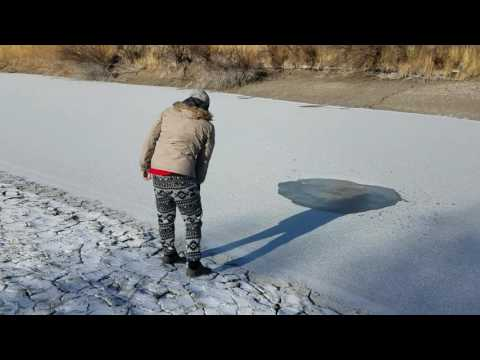 Throwing a big rock in frozen river!  Cracking ice