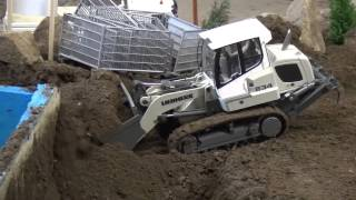 Track loader Liebherr 634 digging out concrete foundations