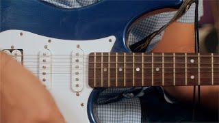 Pan shot of a man playing an electric guitar