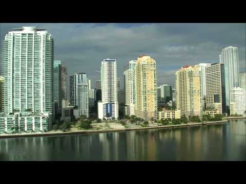 Aerial shot of tall buildings and a harbor in Miami.