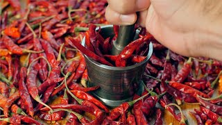 Slow motion video of chef pounding red chilies (lal mirch - Indian spice) in mortar