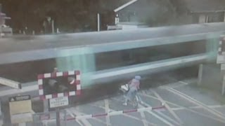 Shocking CCTV: Cyclist narrowly avoids being hit by train at level crossing