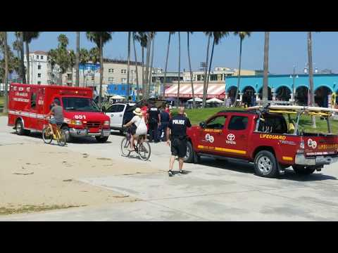LAPD police car runs over a woman in the sand sunbathing at venice beach