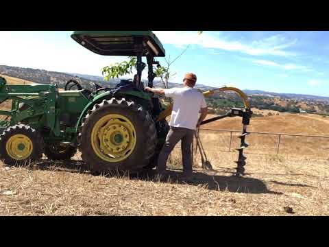 John Deere 4066r drilling holes with the tractor supply country time 3-point auger.