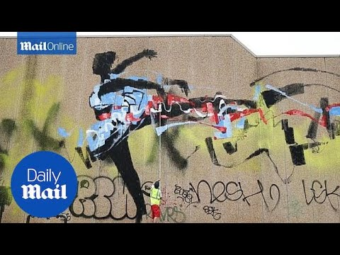 Australian street artist Anthony Lister paints a wall in Sydney