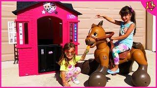 Laurinha brincando com casinha e cavalo elétrico de brinquedo para crianças