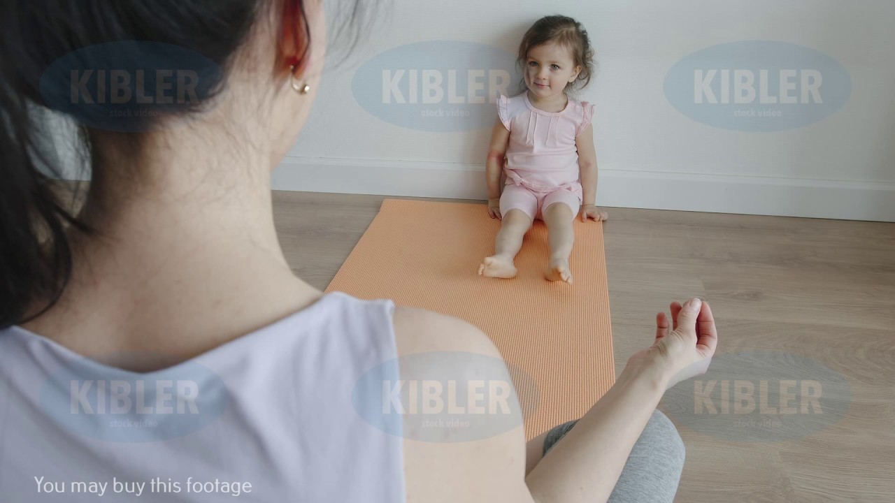 YOGA: Little baby sits near her mom on a yoga mat at home ...