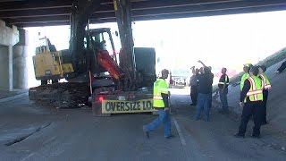 Semi Hauling Construction Equipment Stuck Under Bridge