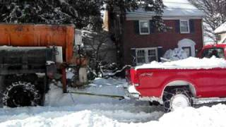 Ford F350 with tire chains pulls International dump truck (snow plow) out of the snow
