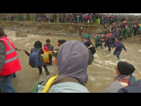 Migrants form human chain across river trying to get to Macedonia