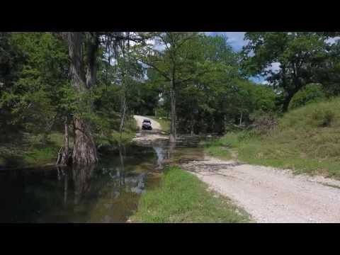Lifted Jeep river crossing at Guadalupe river in Cordiara Ranch Texas