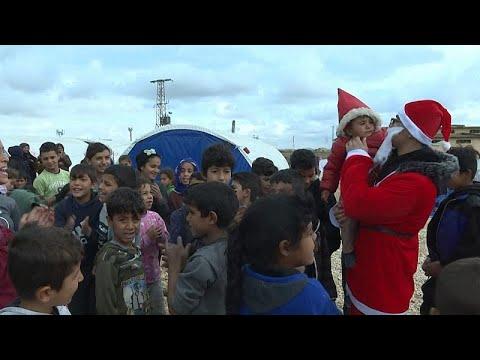 Ativistas distribuem presentes em campo de refugiados sírio