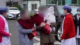 Family cured of coronavirus in Beijing given flowers by hospital