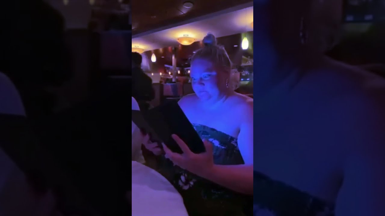 """Woman opening up a bill that shines a blue light as """"Caution"""" by Mariah Carey plays"""
