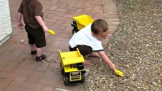 two little boys play with their tonka trucks