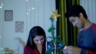 Young adorable couple hanging colorful items/ornaments on a Christmas tree at home
