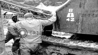 Soldiers attach cable to bulldozer as the bulldozer pulls a truck during World Wa...HD Stock Footage