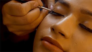 Closeup view of an Indian makeup artist applying eyeliner to a model - makeup concept