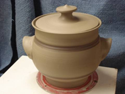 Throwing making a clay pottery casserole with handles and