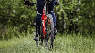 male cyclist riding on green grass in forest