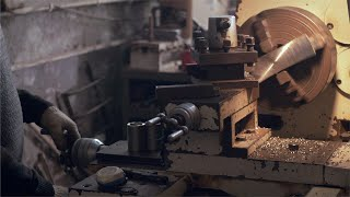 A machine operator operates on old lathe machine