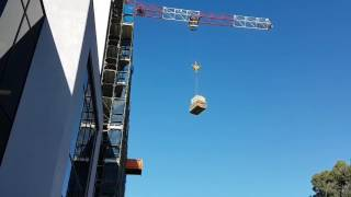 Crane pick heavy load over high rise building