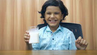 Cute Indian boy sitting at his study table and having milk - healthy food concept