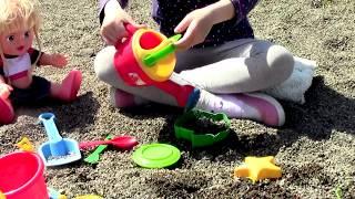 Маша играет с куклами и формочками для песка