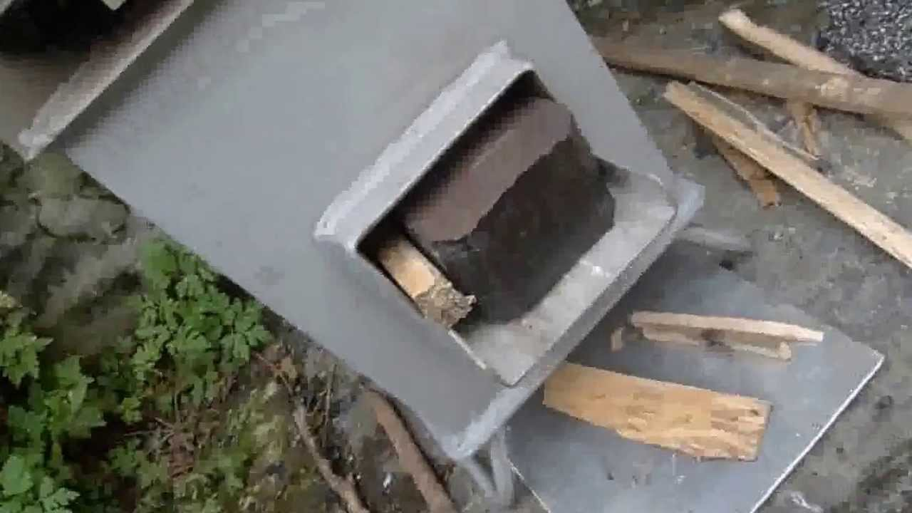 Burning a peat briquette in a stainless steel grover for Heavy duty rocket stove