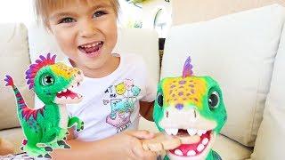 Оливия распаковывает игрушку: это интерактивный питомец динозавр малыш Дино FurReal Friends.