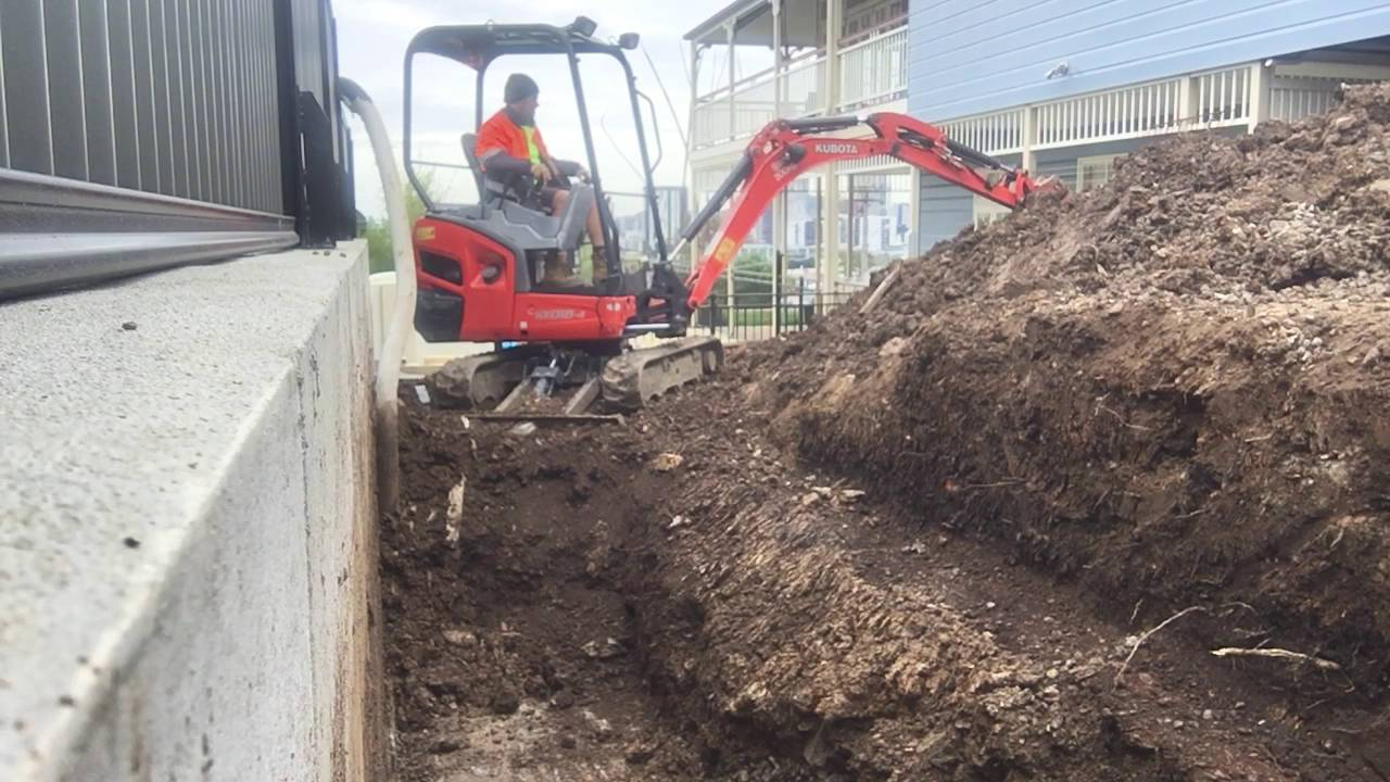 Mini Excavator Digger Digging Out Behind Retaining Wall