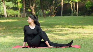 A young girl practicing Vakrasana yoga asana in a park