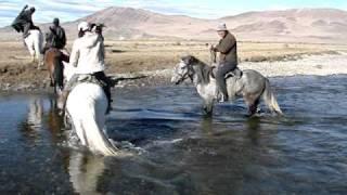 Retour à cheval après journée de chasse avec aigliers mongols...