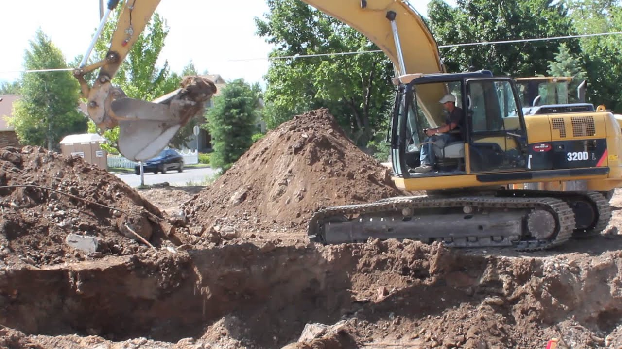Cat 320d excavator digging foundation of building youtube for Digging foundation for house